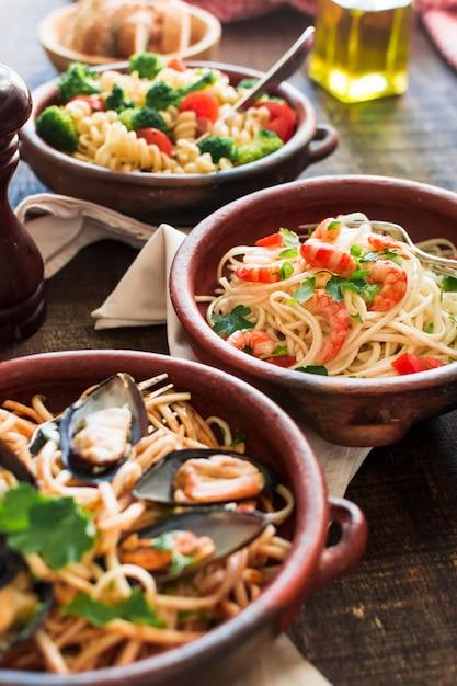 Leckere spaghetti mit garnelen und muscheln im steingut Kostenlose Fotos