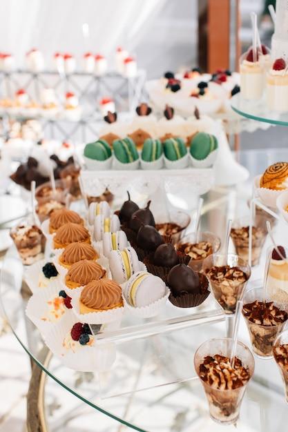 Leckere süßigkeiten am hochzeitssüßigkeitenbuffet mit desserts, cupcakes, tiramisu und keksen Premium Fotos