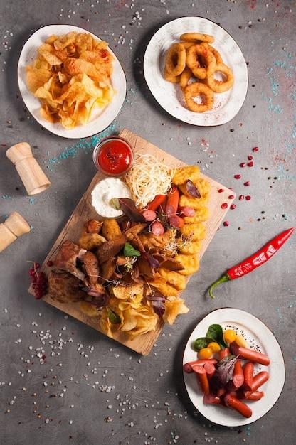 Leckere verschiedene biersnacks: pommes, würstchen, zwiebelringe, hühnernuggets, croutons, geräucherte rippen, hühnerflügel, tomaten-knoblauch-sauce Premium Fotos