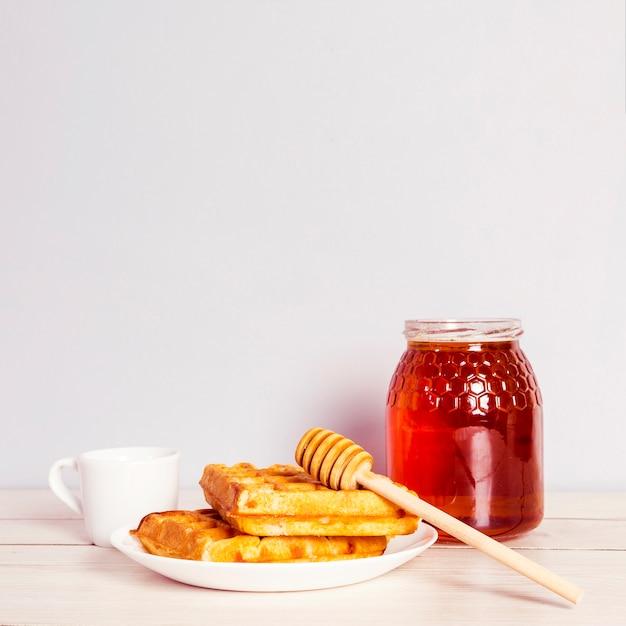 Leckere waffel; glas honig und kaffee zum frühstück auf holztisch Kostenlose Fotos