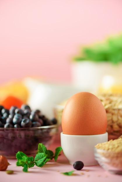 Leckere zutaten für das frühstück. weiches gekochtes ei, haferflocken, nüsse, früchte, beeren, milch, joghurt, orange, banane, pfirsich auf rosa hintergrund. Premium Fotos