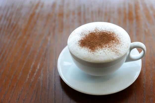 Leckeren heißen cappuccino heißen kaffee in einer weißen tasse in einem restaurant auf einem holztisch mit zimt Premium Fotos