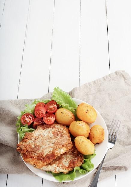 Leckeres abendessen mit steaks, salzkartoffeln und salat Kostenlose Fotos