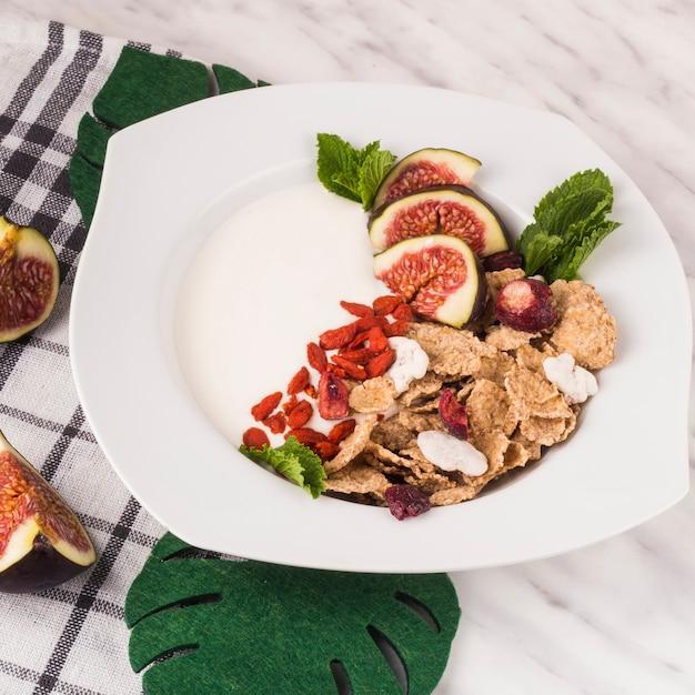 Leckeres frühstück; gefälschte monstera-blätter und feigenscheiben mit küchenserviette über weißer marmoroberfläche Kostenlose Fotos