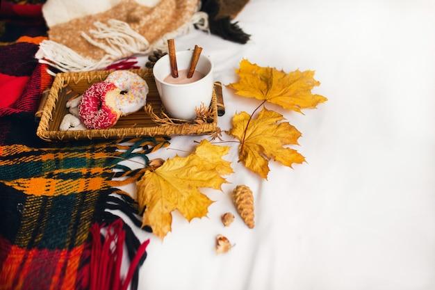 Leckeres frühstück im bett auf holztablett mit tasse kakao, zimt, keksen und glasierten donuts. Kostenlose Fotos