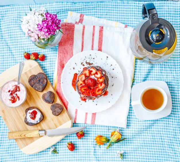 Leckeres frühstück mit teller mit pfannkuchen und erdbeeren Premium Fotos