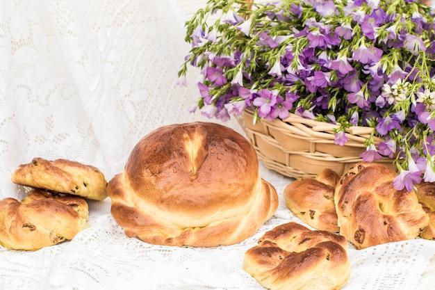 Leckeres gebäck (brot und brötchen mit rosinen) und bouquet-leinen im weidenkorb. retro-stil, vintage Premium Fotos