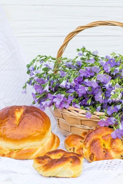 Leckeres gebäck (brot und brötchen mit rosinen) und bouquet-leinen im weidenkorb Premium Fotos