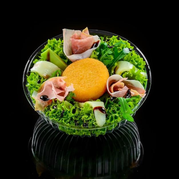 Leckeres gemischtes salatgericht mit gegrilltem camembertkäse, schinken, bio-tomaten und frischen grünen blättern. gesunde fleißige mahlzeit. Premium Fotos
