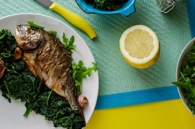 Leckeres italienisches abendessen oder mittagessen mit gebackenen dorada-fischen oder seebrassen, garniert mit spinat auf blauem hintergrund Premium Fotos