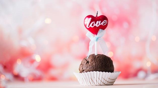 Leckeres muffin mit flammender kerze am zauberstab Kostenlose Fotos