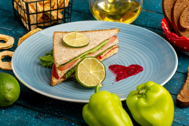 Leckeres sandwich in der blauen platte zusammen mit grünen paprika und öl auf blau Kostenlose Fotos