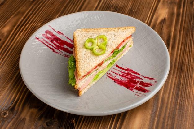 Leckeres sandwich mit grünen salattomaten und schinken in teller auf braun Kostenlose Fotos