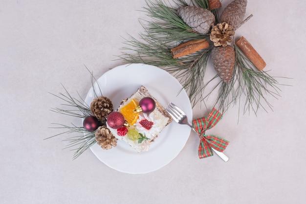 Leckeres stück kuchen mit tannenzapfen und ast des baumes Kostenlose Fotos