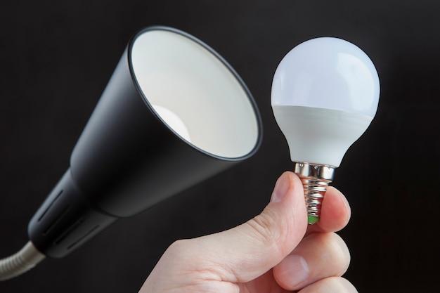 Led elektrische glühbirne in der menschlichen hand nahe lampenschirm stehlampe, gegen dunkelheit. Premium Fotos