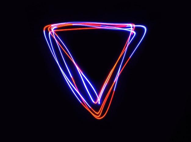 Led-rot- und blaulicht bewegen dreiecksform bei langzeitbelichtung im dunkeln. Premium Fotos