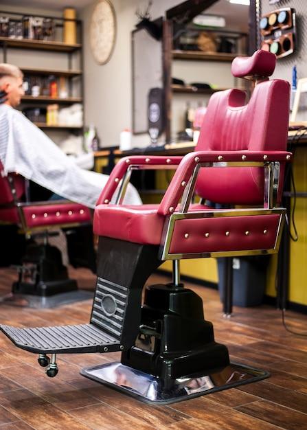 Lederner friseursalonstuhl mit kunden im hintergrund Kostenlose Fotos