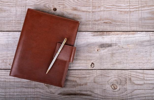 Ledernes geschäftsmann- und stifttagebuch auf hölzernem hintergrund Premium Fotos