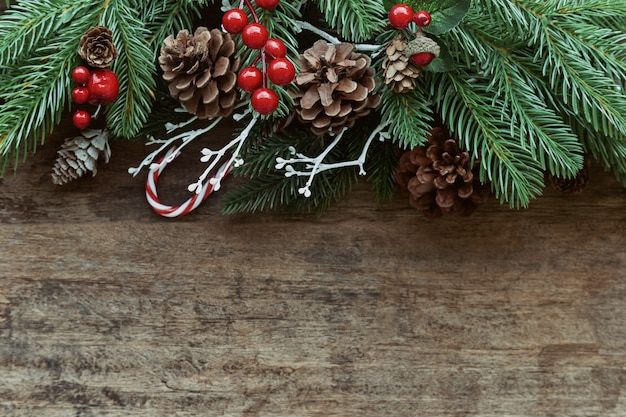 Leere alte hölzerne beschaffenheit verzieren mit kiefernblättern und kegel, stechpalmenbälle, goldener ball und zuckerstange. Premium Fotos