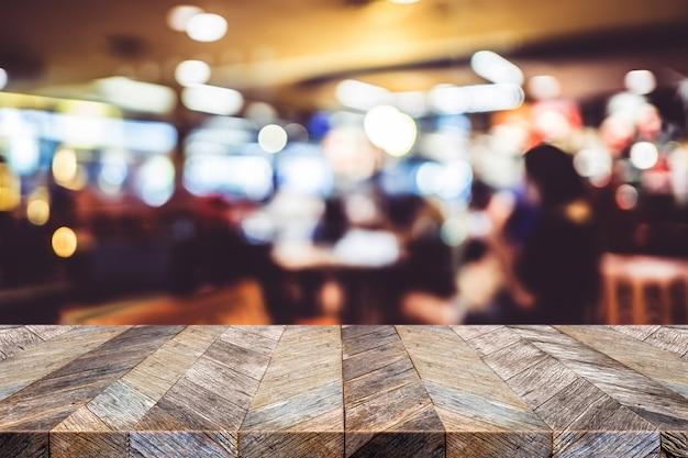 Leere alte hölzerne plankentischplatte des schmutzes mit unschärfeleuteabendessen im restaurant bokeh hintergrund Premium Fotos