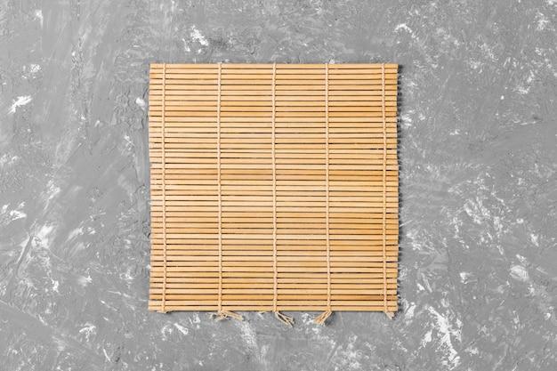 Leere asiatische küche. braune bambusmatte auf draufsicht des hölzernen hintergrundes mit copyspace ebenenlage Premium Fotos