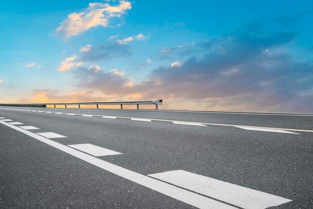 Leere asphaltstraße und naturlandschaft in der untergehenden sonne Premium Fotos