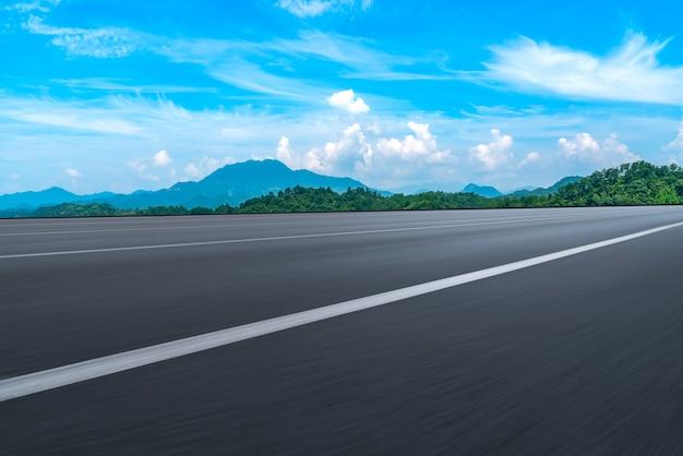 Leere asphaltstraße und naturlandschaft unter dem blauen himmel Premium Fotos