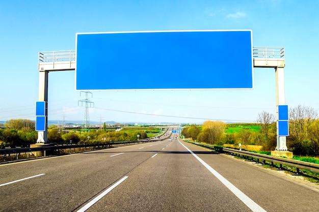 Leere blaue autobahn unterzeichnen vorbei die straße am sonnigen tag Premium Fotos