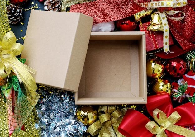 Leere braune beige geschenkbox mit rotem und goldenem weihnachtsschmuck Premium Fotos