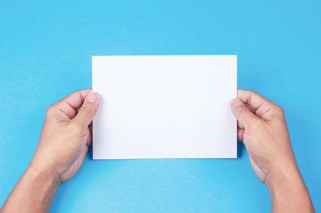Leere broschüre mit freiem raum in der hand auf blauem hintergrund. Premium Fotos