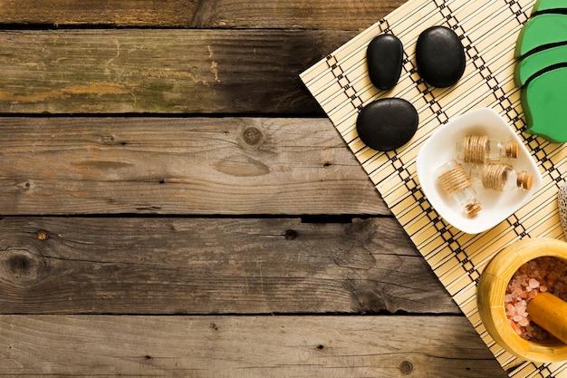 Leere flasche, badesalz und schwarzer kieselstein auf schreibtisch Kostenlose Fotos