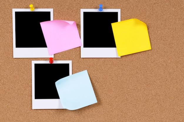 Leere fotoabzüge mit haftnotizen, die an einem korkenbrett befestigt sind. Premium Fotos
