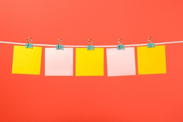 Leere gelbe und rosa papieranmerkungen über die schnur Premium Fotos