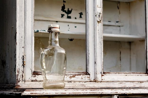 Leere glasflasche auf einem alten weißen küchenschrank Premium Fotos