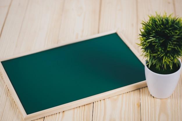 Leere grüne tafel und kleiner dekorativer baum auf holz Premium Fotos
