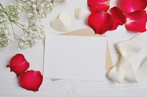 Leere grußkarte oder anmerkung mit blumenzusammensetzung vom gypsophila, von den herzen und von den roten rosafarbenen blumenblättern. valentinstag Premium Fotos