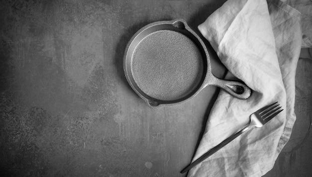 Leere gusseisenpfanne auf dunklem hintergrund Premium Fotos