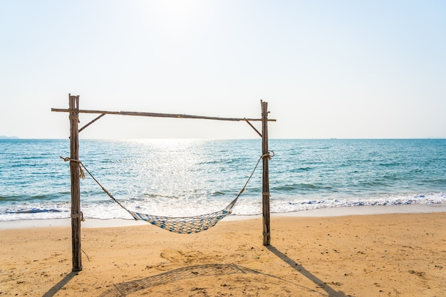 Leere hängemattenschaukel auf dem schönen strand und dem meer Kostenlose Fotos