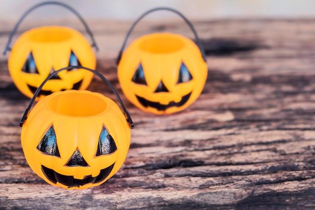 Leere halloween-kürbisgesichtseimer auf alter hölzerner beschaffenheit Kostenlose Fotos