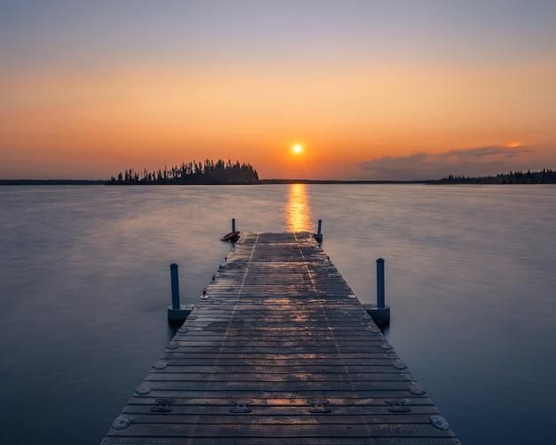 Leere hölzerne anlegestelle in einem see während eines atemberaubenden sonnenuntergangs - ein kühler hintergrund Kostenlose Fotos