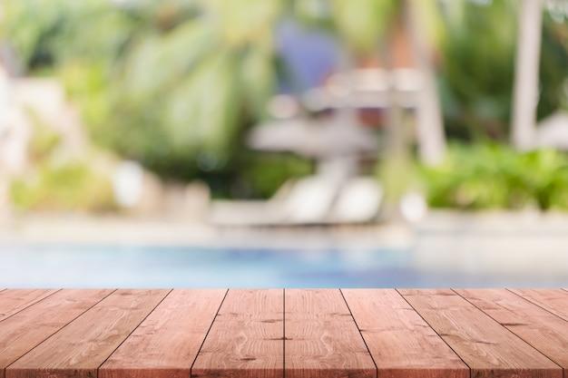 Leere hölzerne tischplatte und unscharfer swimmingpool im tropischen erholungsorthintergrund. Premium Fotos