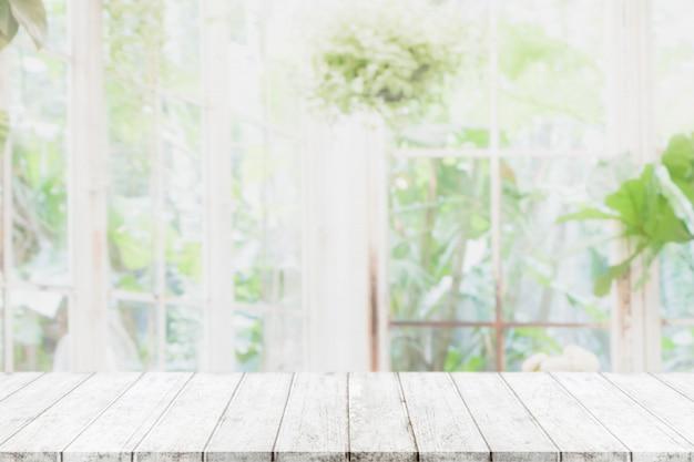 Leere hölzerne tischplatte und verwischt vom innenraum mit fensteransichtgrün vom baumgarten-hintergrundhintergrund Premium Fotos