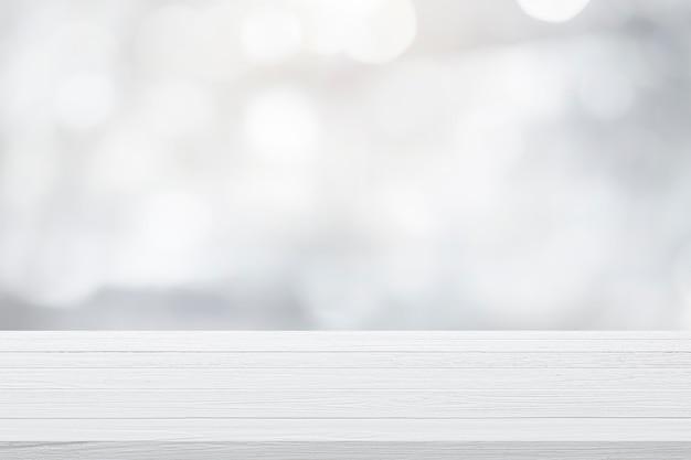 Leere holztabelle für gegenwärtiges produkt auf weißem bokeh-unschärfehintergrund. Premium Fotos