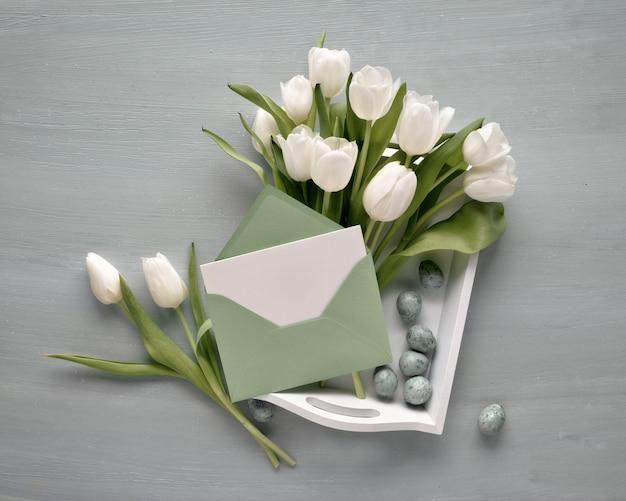 Leere karte im papierumschlag mit dem bündel von weißen tulpen auf dekorativem behälter mit ostereiern Premium Fotos