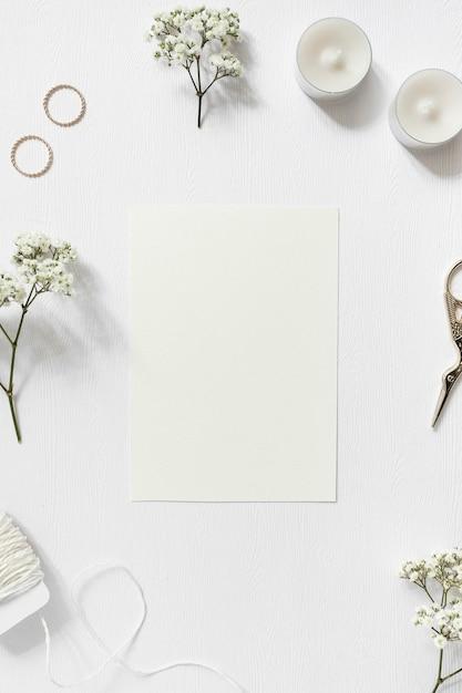 Leere karte mit gypsophila umgeben; eheringe; schnur und schere auf weißem hintergrund Kostenlose Fotos
