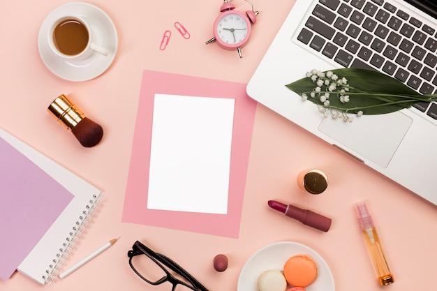 Leere karten mit make-up-produkten, makronen, wecker, kaffeetasse und laptop auf farbigem hintergrund Kostenlose Fotos