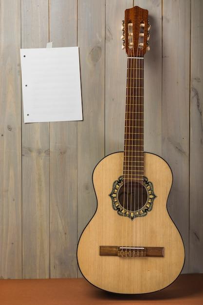 Leere musikalische seite auf hölzerner wand mit gitarre Kostenlose Fotos