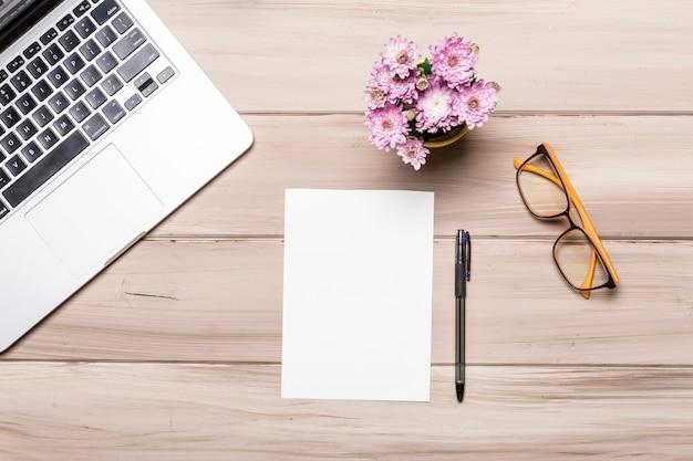 Leere papierblattstiftnotizbuchgläser und -blumen auf tabelle Kostenlose Fotos