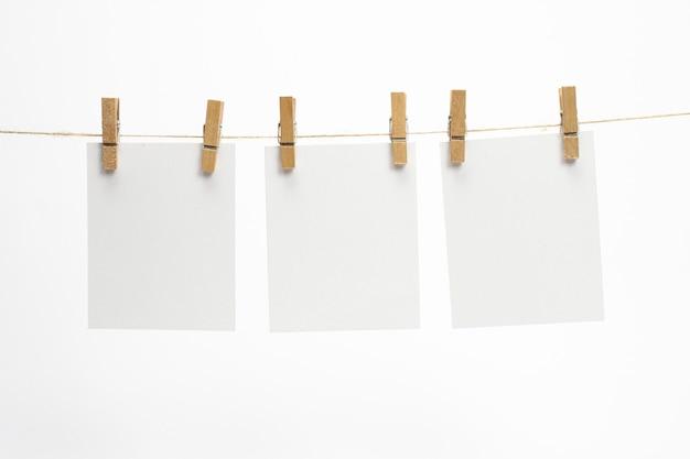 Leere papierrahmen, die mit wäscheklammern an einem seil hängen und auf weiß isoliert sind. leere karten am seil. Kostenlose Fotos