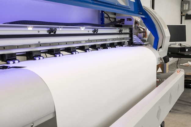 Leere papierrolle in der tintenstrahlmaschine des großen druckerformats für industriegeschäft. Premium Fotos